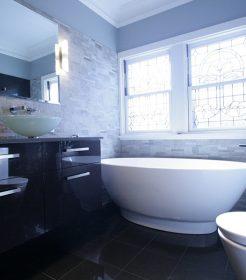 Sydney Bathroom Renovators - black bathroom with black sink cabinet and round white bathtub