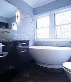Sydney Bathroom Renovators - black bathroom with black sink cabinet and round white bathtub