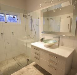 Sydney Bathroom Renovators - Small bathroom with white shower and white cabinets
