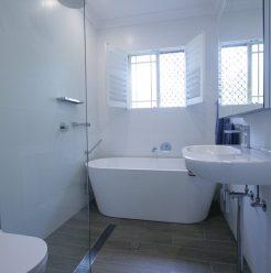 Sydney Bathroom Renovators - Small white bathroom with bathtub at the end