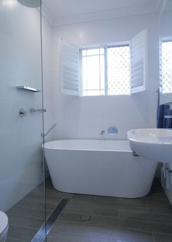 Sydney Bathroom Renovators - Small white bathroom with bathtub at the end