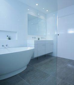 Sydney Bathroom Renovators - bathroom with grey flooring tiles and white walls - view on bathtub